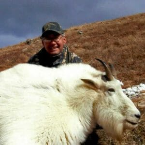 Huge mountain goat and hunter posing after hunt.